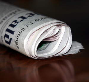 This is a picture of a rolled up newspaper on a table.
