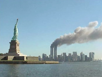 This is a picture of the statue of liberty with the twin towers burning in the background.