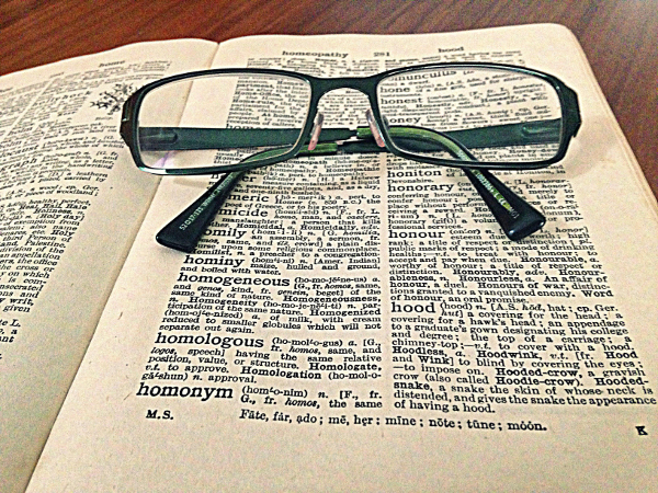 A picture of a pair of glasses resting on an open book.